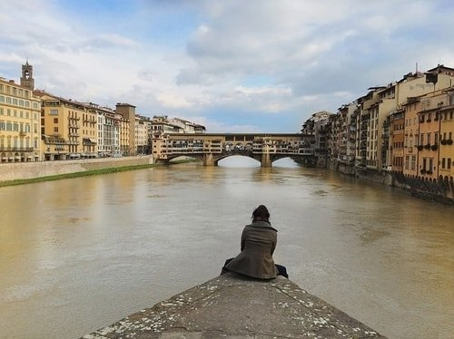 woman looking at old bridge in italy
