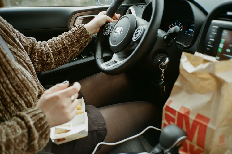 A person driving car with snacks