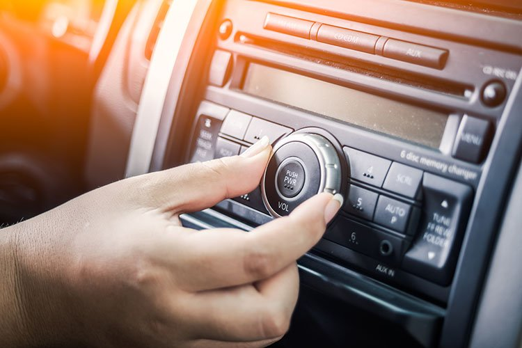 A person turning the volume of music in car