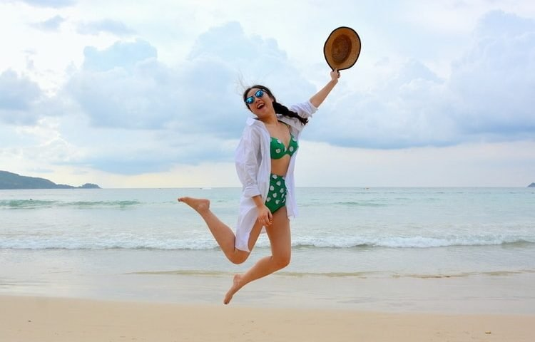 woman on beach wearing long sun protection clothing