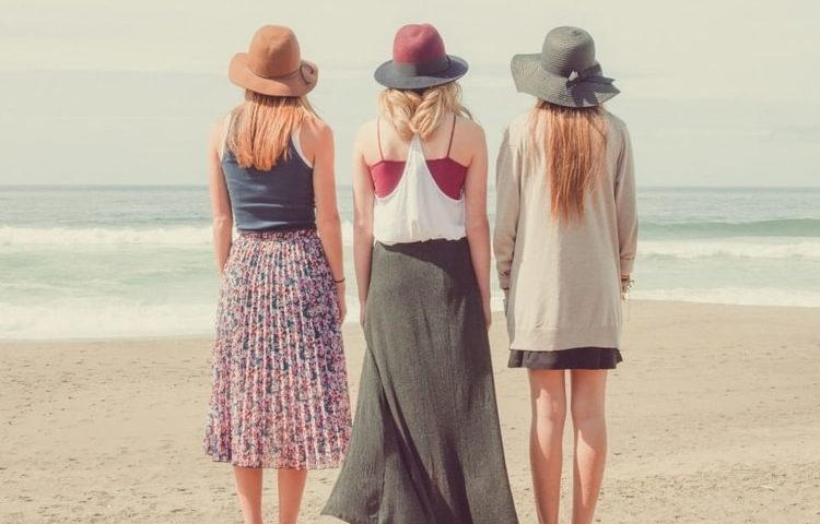 3 women on beach wearing hats